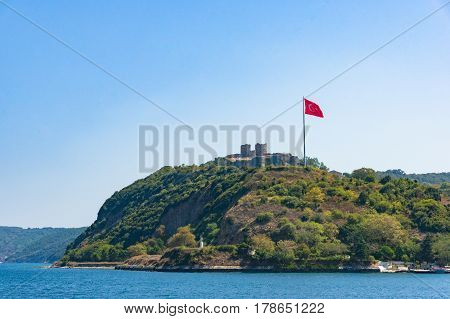 Anadolu castle with Turkish flag on sunny day. Turkey
