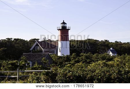 Nauset Lighthouse, Eastham, Massachusetts - September 12, 2014 - Wide view of Nauset Lighthouse in Eastham, Massachusetts with the main house and foliage on a bright sunny day with blue skies and clouds in September.