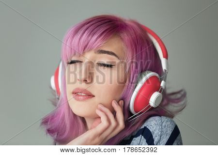 Beautiful young woman with dyed hair listening music on color background