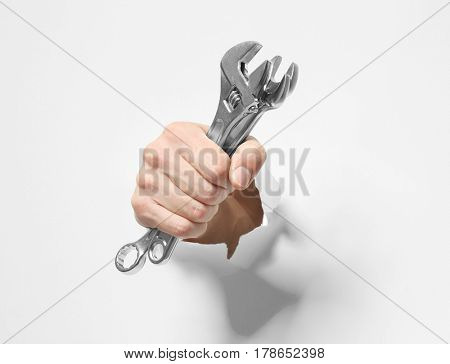 Hand of auto mechanic with tools tearing white paper background