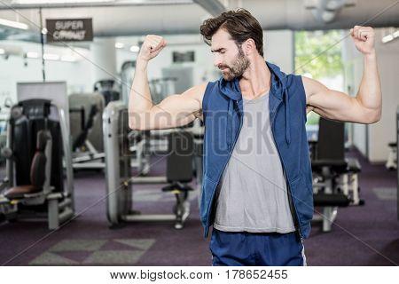 Muscular man showing biceps at the gym