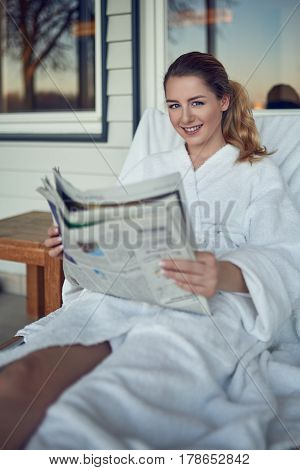 Attractive smiling young woman at a spa resort relaxing on a recliner bed on a patio in a clean white bathrobe reading a newspaper