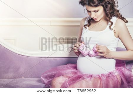 Young Beautiful Pregnant Woman With Pink Knitted Booties And A Pink Ballet Skirt