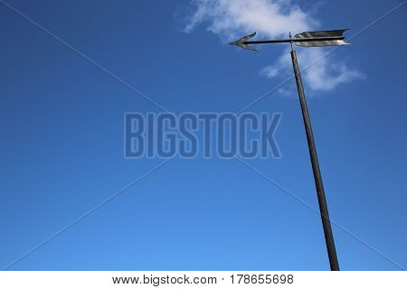 Weather Vane or Wind Direction Indicator against blue Sky