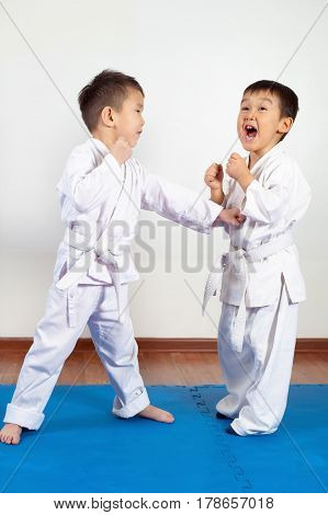 Two boys girls demonstrate martial arts working together. Fighting position active lifestyle practicing fighting techniques