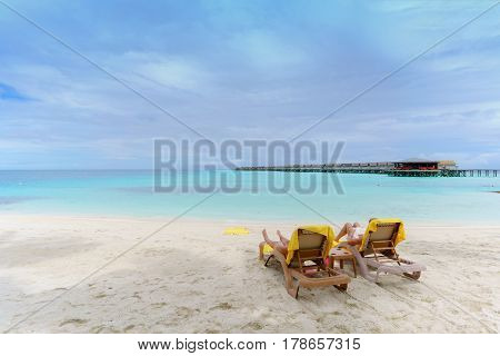 Tourists sunbathing and reading book on the beach in tropical Maldives island