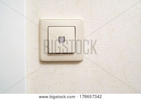 Illuminated beige light switch mounted on wall