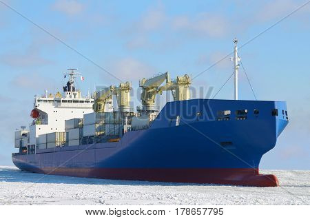 Big cargo ship floats on the Bay.Under its weight breaks the ice.