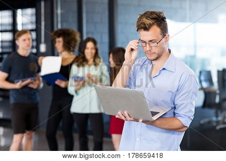 Man using a laptop while colleagues standing behind in office