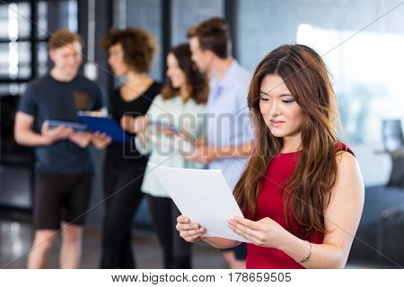 Woman reading a document while her colleagues standing behind in office