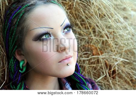 close-up portrait of young stylish woman with green eyes on haystack background