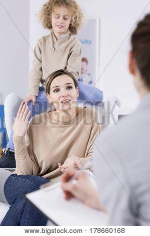 Boy Sitting Behind Mother