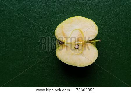 longitudinal cut or section of one apple as the isolated object closeup on green or against a dark background