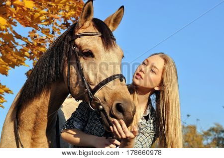 portrait of teenage girl and horse in autumn day