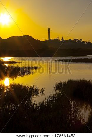 El Rompido lighthouse and marina at sunrise from marshlands Huelva Spain