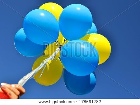 bunch of the yellow and blue balloons in the human hand on the blue sky background