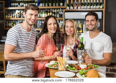 Friends holding glasses of white wine and looking at camera