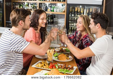 Friends toasting with white wine at bar