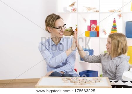 Girl And Speech Therapist Giving Each Other High Five