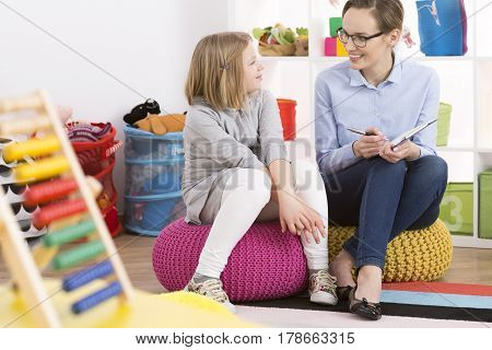 Girl And Psychologist Sitting On Poufs