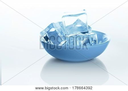 Transparent ice cubes in bowl on white background. Closeup of cold crystal block with water drops