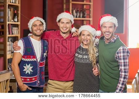 Friends wearing Christmas hats in a bar