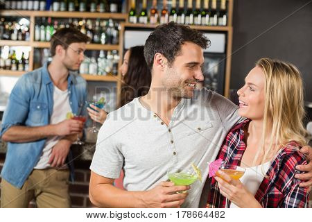 Couple toasting with cocktails with other couple talking behind