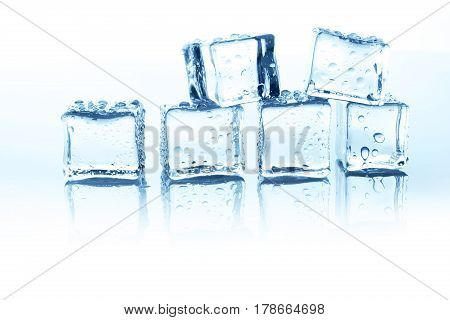 Transparent ice cubes group on white background. Closeup of cold crystal block with water drops
