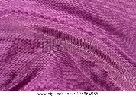 Silk background texture of magenta shiny fabric close up