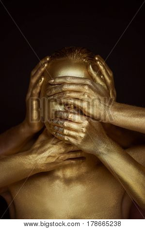 Girl painted gold. 6 hands on your face: see no evil, hear no evil, speak no evil.