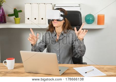 Businesswoman With Vr Headset And Laptop In Workplace