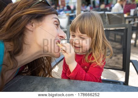 Child Feeding Mother With Cheese Puff In Exterior Bar