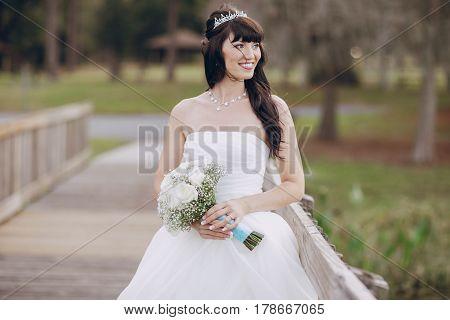 beautiful wedding bride on a bridge near the lake in a cloudy weather