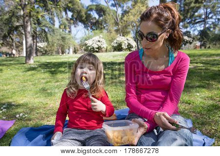 Mother And Child Sitting In Park Eating Pasta