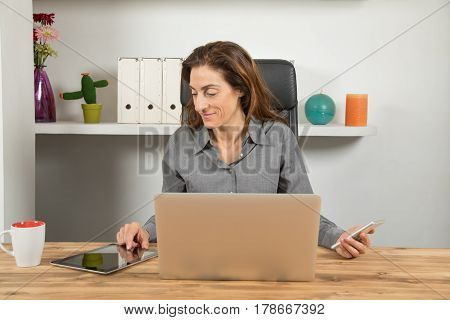 Multitasking Businesswoman With Tablet Phone And Laptop
