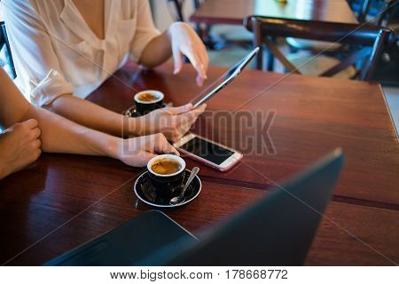Close Up Of Two Female Model's Hands Using Smart Devices While Having Coffee In A Coffee Shop As Par