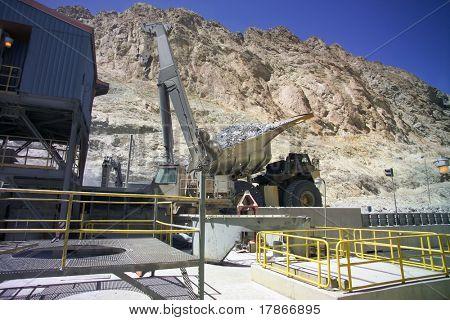 A big mining truck drops copper mineral into cruncher
