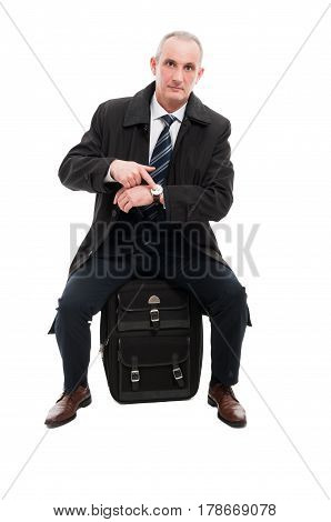 Middle Age Business Man Showing Watch Sitting On Luggage