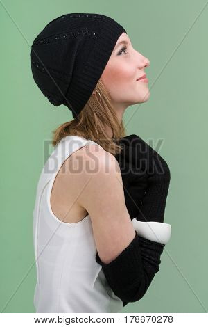 knitwear. young woman wearing a winter cap and gloves, isolated on green background
