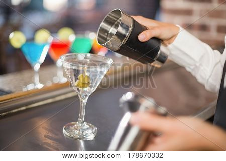 Feminine bartender hand pouring a cocktail in a bar