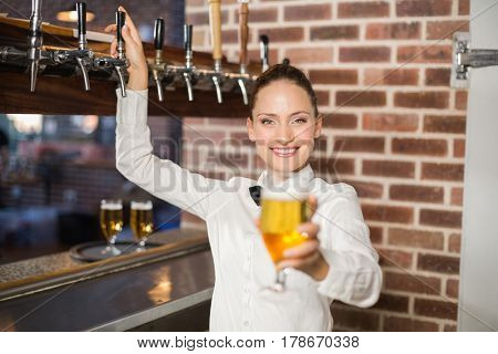 Attractive barmaid holding a beer in a bar
