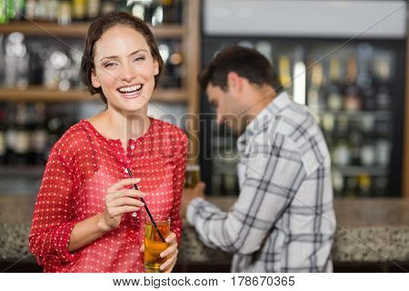 Attractive woman smiling at camera holding a beer