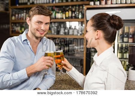 Attractive man and barmaid toasting with beers with man looking at camera