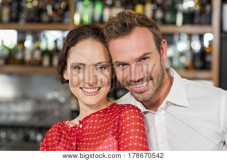 Attractive couple smiling at camera while hugging at a bar