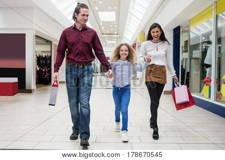 Happy family walking with shopping bags in mall
