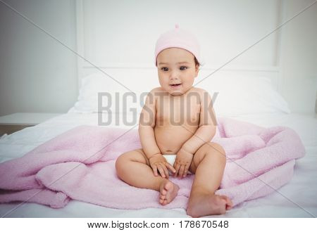 Full length of cute baby sitting on bed at home
