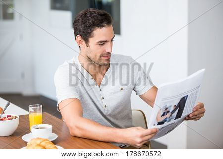 Man reading newspaper while sitting at table