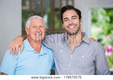 Portrait of smiling father and son with arm around wile standing at home