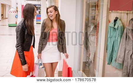 Two happy women with shopping bags window shopping in mall