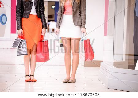 Women standing with bags while shopping in mall